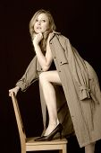 stock photo of implied nudity  - attractive lady with leg on chair wearing only a trenchcoat - JPG
