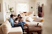 Young Hispanic family sitting on sofa reading a book together in the living room, seen from doorway poster