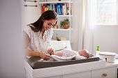 Happy mother changing the diaper of her newborn son at home on changing table, selective focus poster