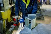 Worker In Metalworking Plant Installing A Rivets Into Part For Construction Ducts Of Industrial Air  poster