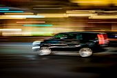 Black Suv Traveling Fast With Motion Blur And City Lights Concept poster