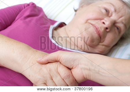 Senior Lying In Bed And Welcomes Nurse
