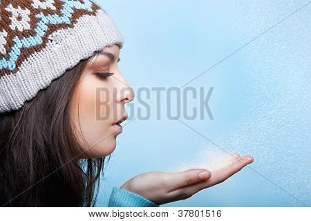 woman blows the snow