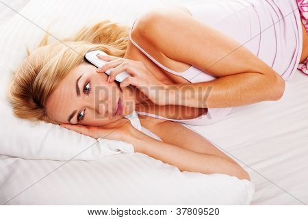 Woman In Bed On Her Mobile