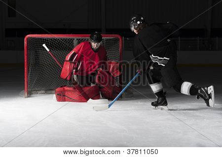 Ice Hockey Goalie With Skaters Shooting Puck
