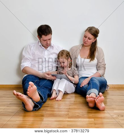 Happy Family Sitting On The Floor Against The Wall And Using Tablet Computer