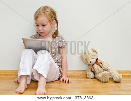 Cute Little Girl Sitting On The Floor Against The Wall And Using Tablet Computer