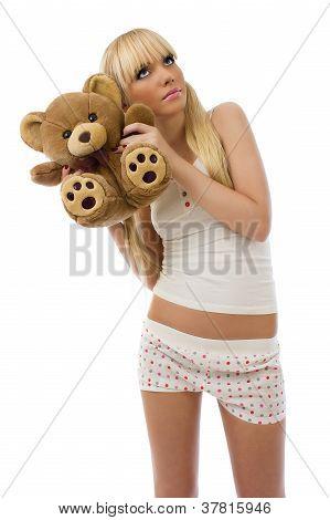 Blonde Girl Wearing Pajamas Embraces Teddy Bear
