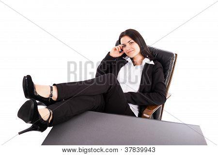 Junge geschäftsfrau im Lehnstuhl mit Beinen auf Tisch