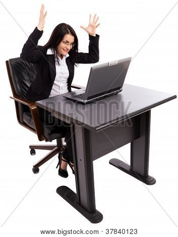 Angry Businesswoman Sitting At Desk While Using A Laptop