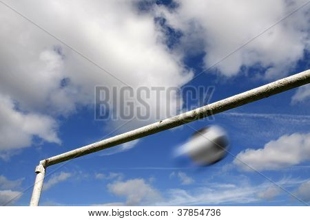 Blurred Football And Goalpost Against A Cloudy Sky