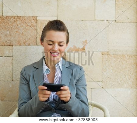 Happy Business Woman Writing Text Message On Cell Pone