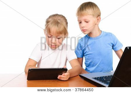 Elementary Boy And Girl Sitting At Table Using Digital Pad And Laptop