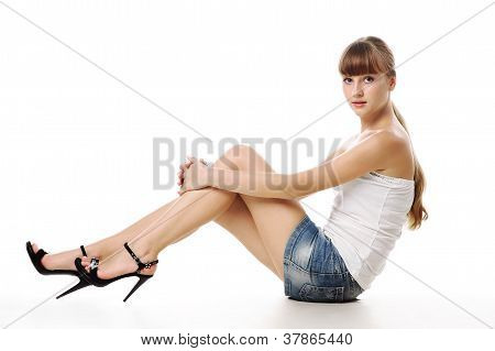 Beautiful Stylish Teen Girl Sitting Isolated Over A White Background