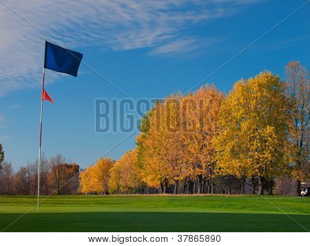 Golf Blue Flag On Green In Fall