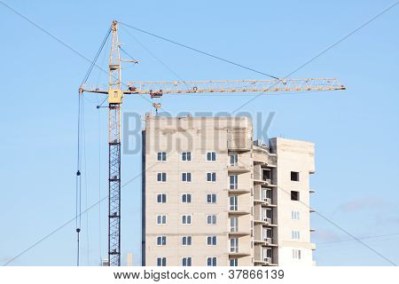 crane building a new house on a background of blue sky
