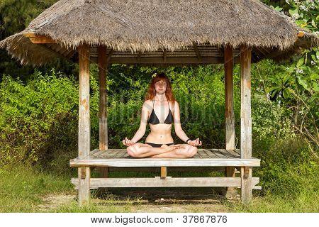 Woman Doing Yoga Meditation In Tropical Gazebo