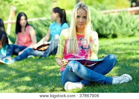 Beautiful Female Student Learns Outside On Green Lawn