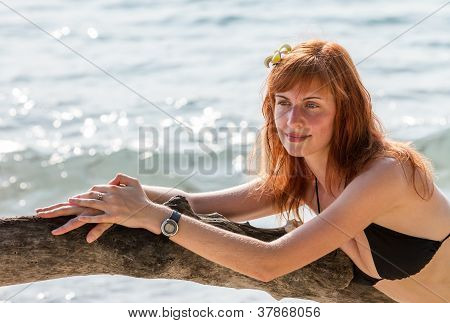 Woman In Bikini Posing On Branchy Log In Water