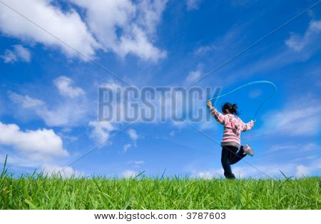 Young Girl Skipping In Green Grassland