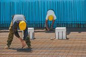 stock photo of reinforcing  - Authentic construction workers installing binding wires to reinforcement steel bars in front of a blue insulated surface prior to pouring concrete - JPG