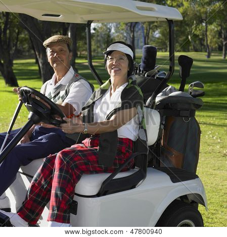 Senior couple sitting in golf cart