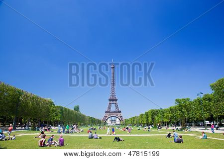 PARIS - JUNE 7 : Tourists and locals take advantage of sunny summer weather on Champ de Mars next to the Eiffel Tower on June 7, 2013, Paris, France