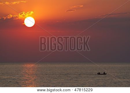 Sunset With Silhouettes Of Paddling Boat
