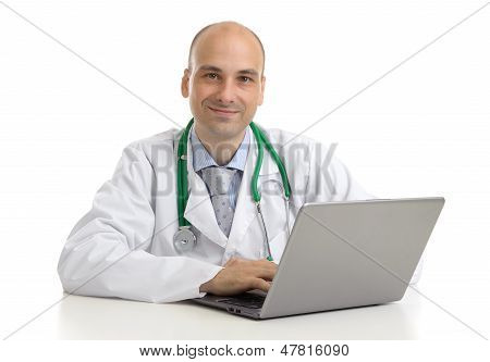 Cheerful Doctor Sitting At The Desk Working On Laptop