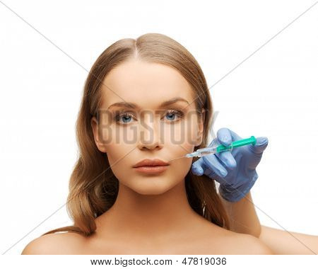 cosmetic surgery concept - woman face and beautician hand with syringe