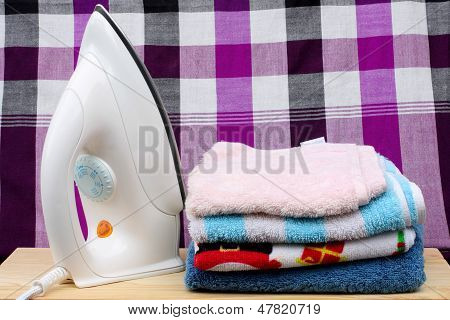 loinclothPile of colorful clothes and electric iron on loincloth background