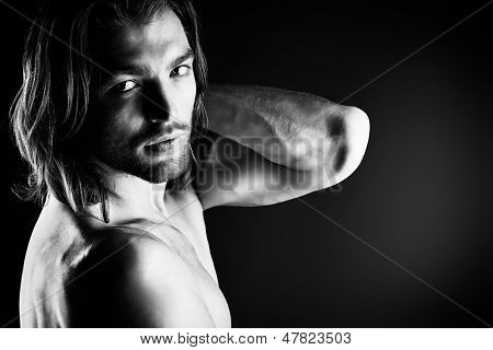Portrait of a sexual muscular nude man posing over dark background.