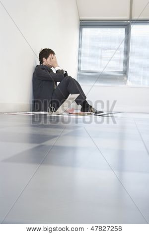 Side view of a despaired businessman sitting on floor