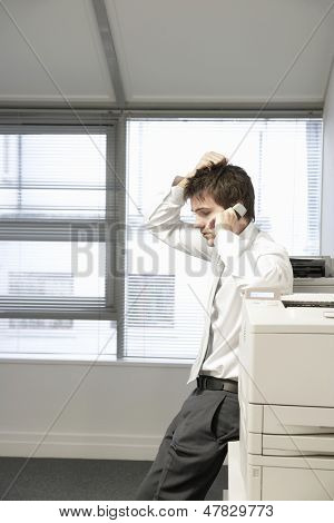 Side view of an uncertain businessman leaning on office photocopier and using cellphone