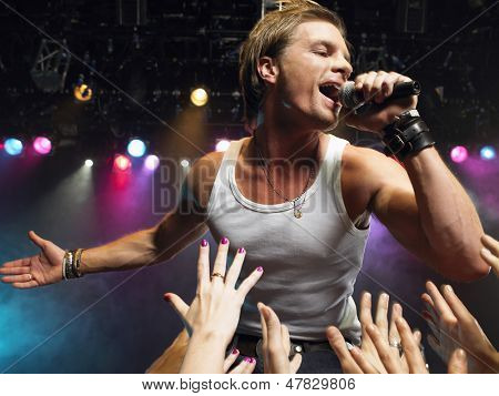 Young man singing on stage in concert with adoring fans reaching towards him