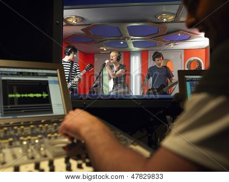 Band in recording studio with technician in foreground