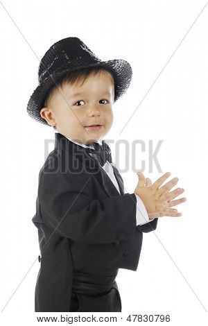 Closeup side view of a toddler in a black tuxedo and a sparkly fedora.  On a white background.