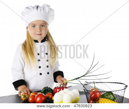A pretty young girl before a table full of eggs and veggies.  She's wearing a chef's jacket and hat.  On a white background.