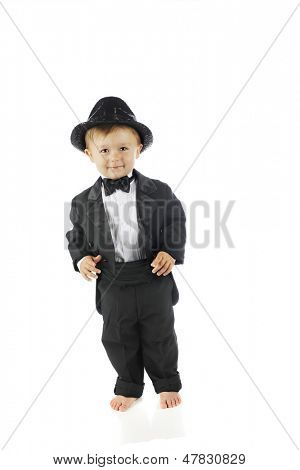 An adorable barefoot toddler all decked out in a black tuxedo and sparkly fedora.  On a white background.