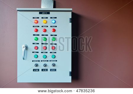 Electric control on brown wall