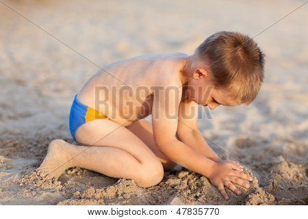 Niño jugando construyendo castillos de arena en la playa