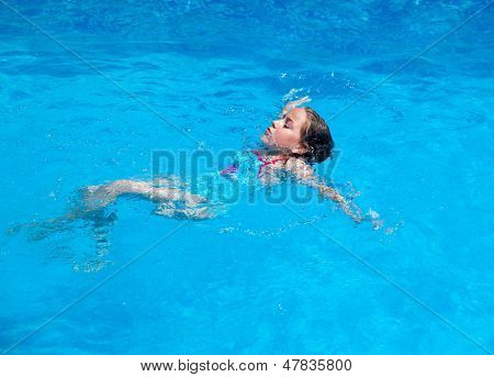 Child swimming backstroke in the swimming pool