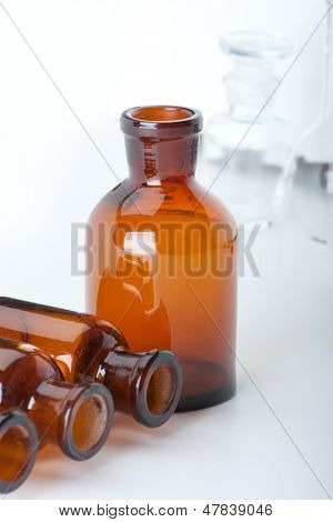 Small chemical glass bottles on white background