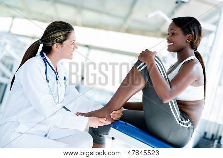 Gym doctor with a patient checking her ankle