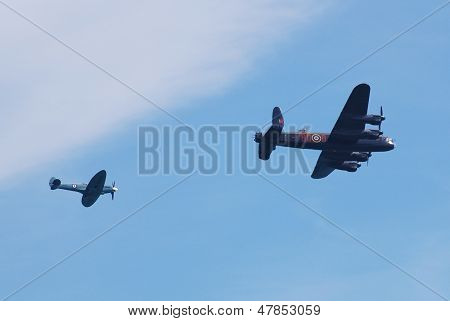 EASTBOURNE, ENGLAND - AUGUST 11: Lancaster bomber PA474 and Spitfire PS915, of the Battle of Britain Memorial Flight, perform at the Airbourne airshow on August 11, 2012 in Eastbourne, East Sussex.