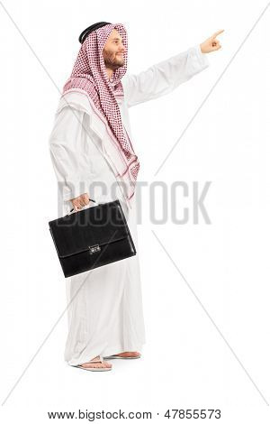 Full length portrait of a male arab person holding a leather suitcase and pointing isolated on white background