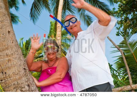 Happy Mature Couple With Snorkeling Gear Waving