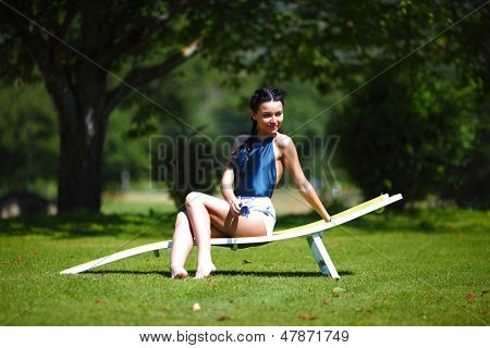 girl sitting in a white lounge on a green gras