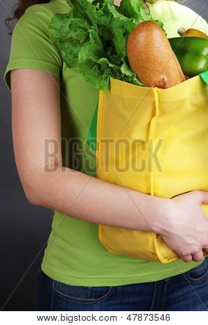 Girl with shopping bag on grey background