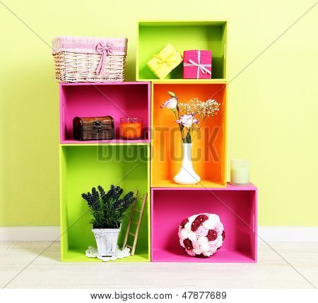 Shelves of different bright colors with decorative addition on wall background